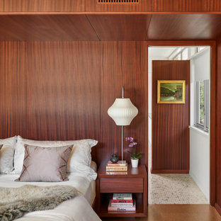 Inspiration for a mid-sized midcentury master bedroom in Austin with brown walls, cork floors, no fireplace, brown floor, wood and wood walls.