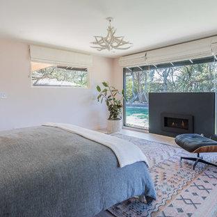 На фото: хозяйские спальни в стиле ретро с белыми стенами, светлым паркетным полом, горизонтальным камином, фасадом камина из бетона и бежевым полом
