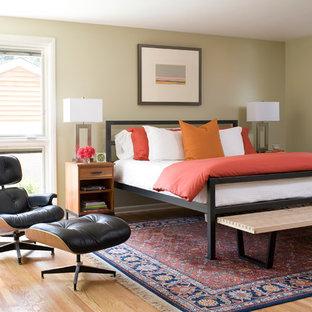 Inspiration pour une chambre parentale design avec un sol en bois clair et un mur vert.
