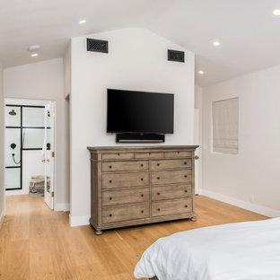 ロサンゼルスの広いトランジショナルスタイルのおしゃれな主寝室 (白い壁、淡色無垢フローリング、標準型暖炉、レンガの暖炉まわり、茶色い床、三角天井) のインテリア