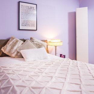 Foto de dormitorio minimalista, de tamaño medio, sin chimenea, con paredes púrpuras y suelo de madera en tonos medios