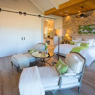 Foto på ett mellanstort 50 tals gästrum, med grå väggar, ljust trägolv, en standard öppen spis och en spiselkrans i tegelsten
