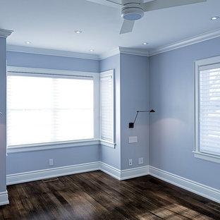 Modelo de dormitorio principal, clásico, pequeño, con paredes azules, suelo de madera en tonos medios, chimenea de doble cara y marco de chimenea de yeso