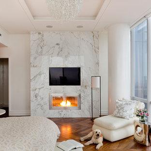 Modernes Hauptschlafzimmer mit beiger Wandfarbe, dunklem Holzboden, Gaskamin und Kaminumrandung aus Stein in New York