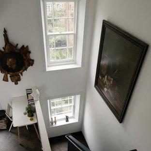 ロンドンの大きいコンテンポラリースタイルのおしゃれな主寝室 (白い壁、合板フローリング、標準型暖炉、漆喰の暖炉まわり、茶色い床) のインテリア