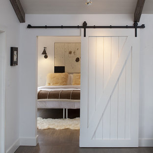 Photo of a country bedroom in San Francisco with white walls and dark hardwood floors.