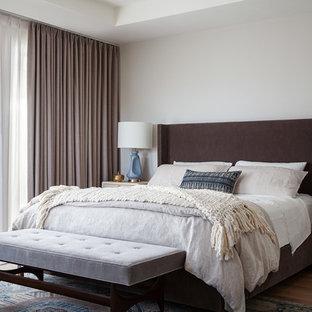 Aménagement d'une chambre parentale classique avec un mur blanc, un sol en bois brun et un sol marron.