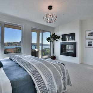 Foto di una grande camera matrimoniale minimalista con pareti bianche, moquette, camino bifacciale e pavimento bianco