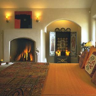 Свежая идея для дизайна: хозяйская спальня среднего размера в средиземноморском стиле с бежевыми стенами, стандартным камином, фасадом камина из штукатурки, бетонным полом и бежевым полом - отличное фото интерьера