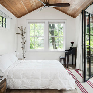 Bedroom - farmhouse light wood floor and beige floor bedroom idea in Austin with white walls