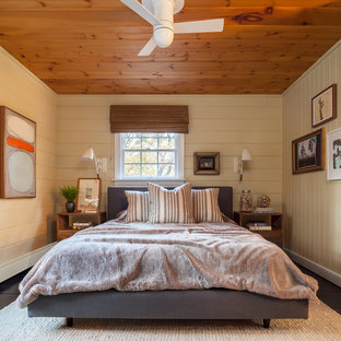 Photo of a country bedroom in New York with yellow walls, dark hardwood floors and brown floor.