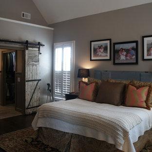 Imagen de dormitorio principal, rústico, de tamaño medio, sin chimenea, con paredes grises, suelo de madera oscura y suelo marrón