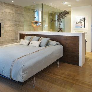 Неиссякаемый источник вдохновения для домашнего уюта: спальня в современном стиле с паркетным полом среднего тона, горизонтальным камином и фасадом камина из камня