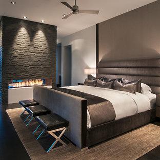 Modernes Hauptschlafzimmer mit weißer Wandfarbe, dunklem Holzboden, Kaminumrandung aus Stein und Tunnelkamin in Phoenix