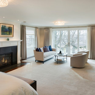 Immagine di una camera matrimoniale classica di medie dimensioni con pareti beige, parquet scuro, camino classico, cornice del camino in intonaco e pavimento marrone