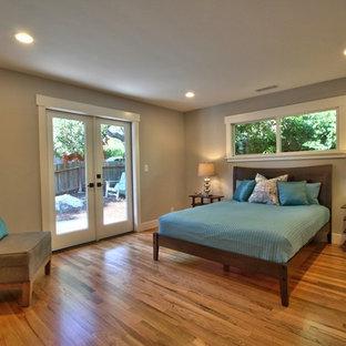 Ejemplo de dormitorio principal, tradicional renovado, de tamaño medio, con paredes grises, suelo de madera en tonos medios y suelo marrón