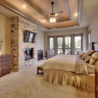Foto di una camera da letto rustica con pareti beige, moquette, camino classico e cornice del camino in pietra