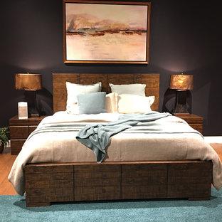 Modelo de dormitorio principal, contemporáneo, de tamaño medio, sin chimenea, con paredes negras y suelo de madera en tonos medios