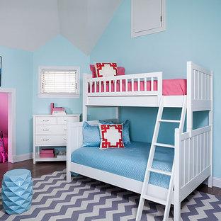 Diseño de dormitorio tipo loft, actual, de tamaño medio, con paredes azules, suelo de madera en tonos medios y suelo gris