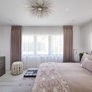 Example of a large trendy guest porcelain tile and gray floor bedroom design in Miami with no fireplace and white walls