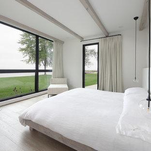Minimalist master light wood floor bedroom photo in Milwaukee with white walls