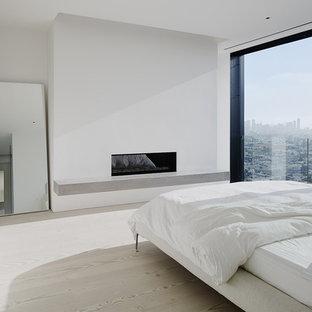 Imagen de dormitorio principal, moderno, de tamaño medio, con suelo de madera clara, chimenea lineal y marco de chimenea de yeso