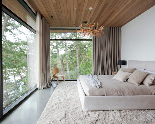 Inspiration for a large modern master concrete floor bedroom remodel in  Vancouver with white walls