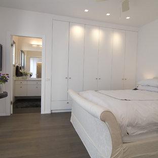 Immagine di una camera da letto minimalista con pareti bianche e parquet scuro