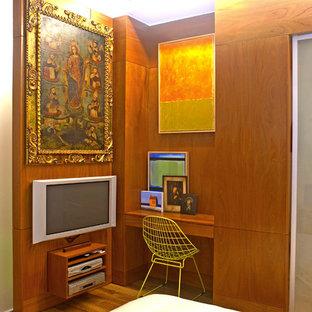 Example of a minimalist medium tone wood floor bedroom design in Newark with brown walls