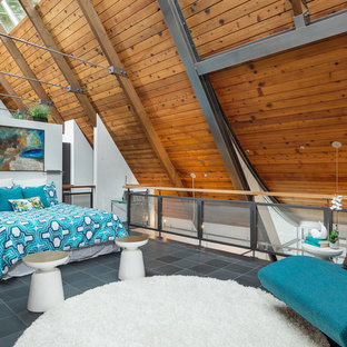 Design ideas for a large contemporary loft-style bedroom in Seattle with white walls and slate floors.