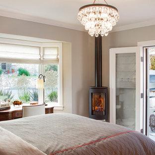 Ispirazione per una camera matrimoniale classica con pareti grigie, pavimento marrone, parquet scuro, camino sospeso e cornice del camino in metallo