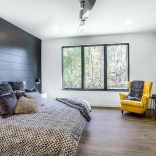 Esempio di una camera da letto design con pareti nere, parquet chiaro e nessun camino