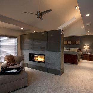 Modelo de dormitorio principal, contemporáneo, grande, con paredes grises, moqueta, chimenea de doble cara, marco de chimenea de metal y suelo beige