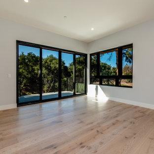 Foto de habitación de invitados minimalista, grande, con paredes grises, suelo de madera clara y suelo blanco
