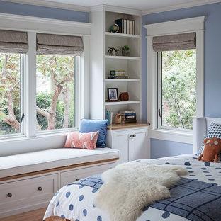 Aménagement d'une chambre d'amis craftsman de taille moyenne avec un mur bleu, un sol en bois brun, aucune cheminée et un sol marron.