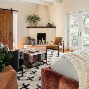 Diseño de dormitorio principal, moderno, con paredes blancas, suelo de madera en tonos medios, chimenea de esquina y marco de chimenea de ladrillo