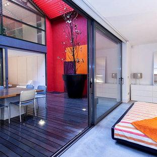Modelo de dormitorio principal, ecléctico, grande, con marco de chimenea de yeso, suelo de cemento, paredes blancas y suelo gris