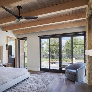 На фото: хозяйская спальня среднего размера в стиле кантри с белыми стенами, паркетным полом среднего тона, стандартным камином, фасадом камина из металла, коричневым полом и деревянным потолком с