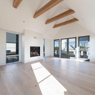 Imagen de dormitorio principal, contemporáneo, grande, con paredes blancas, suelo de madera clara, chimeneas suspendidas, marco de chimenea de yeso y suelo blanco