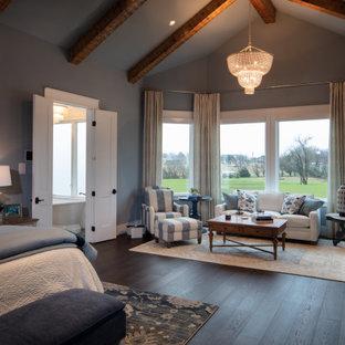 Ejemplo de dormitorio principal, de estilo de casa de campo, grande, con paredes azules, suelo de madera en tonos medios, chimenea tradicional, marco de chimenea de hormigón y suelo marrón