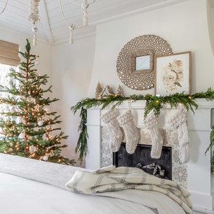 Lantlig inredning av ett sovrum, med vita väggar, en standard öppen spis och en spiselkrans i trä