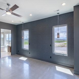 На фото: со средним бюджетом большие хозяйские спальни в стиле кантри с черными стенами, бетонным полом, стандартным камином, фасадом камина из штукатурки и серым полом