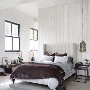 Esempio di una camera da letto stile loft country di medie dimensioni con pareti bianche, pavimento in cemento e pavimento grigio