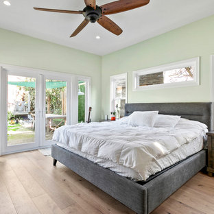 Inspiration for a mid-sized cottage master light wood floor and beige floor bedroom remodel in Los Angeles with green walls