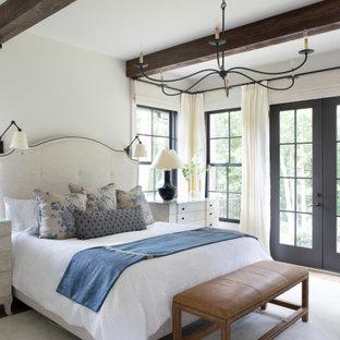 Cette image montre une grand chambre parentale rustique avec un mur blanc, aucune cheminée, un sol en bois clair et un sol beige.