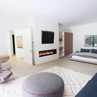 На фото: хозяйская спальня в скандинавском стиле с белыми стенами, горизонтальным камином и фасадом камина из штукатурки с