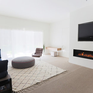 На фото: хозяйская спальня в стиле модернизм с белыми стенами, ковровым покрытием, горизонтальным камином и фасадом камина из штукатурки с