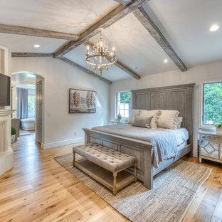 Immagine di una camera matrimoniale tradizionale con pareti bianche, pavimento in legno massello medio, camino classico, pavimento marrone, travi a vista e soffitto a volta