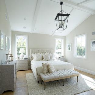 Cette image montre une grande chambre parentale rustique avec un mur blanc, un sol en bois brun, un sol marron et aucune cheminée.