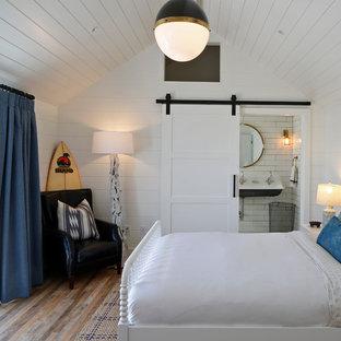 Imagen de dormitorio costero, sin chimenea, con paredes blancas y suelo de madera en tonos medios